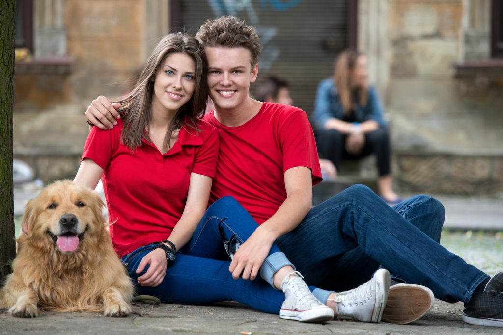Couple of teenagers in love posing with a golden retriever